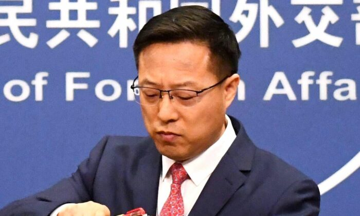Chinese Foreign Ministry spokesman Zhao Lijian packs up his notes after speaking at the daily media briefing in Beijing on April 8, 2020. (Greg Baker/AFP via Getty Images)
