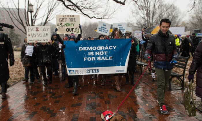 Demonstrators march in the snow through Lafayette Park, outside the White House, during a rally against the Supreme Court's 2010 decision in favor of Citizens United, which allows private citizens and corporations to make unlimited donations for political campaigns, on Jan. 21, 2015.  (NICHOLAS KAMM/AFP via Getty Images)