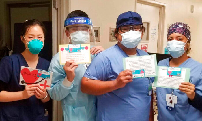 "Health care workers hold thank-you cards from the ""Cards 4 COVID Heroes"" initiative at Los Angeles Community Hospital in Los Angeles on June 30, 2020. (Keith Levy via AP)"