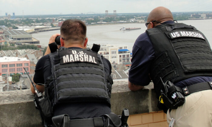 Two U.S. Marshals stand on a building as they look out toward the city in a file photo. (Illustration - Elliott Cowand Jr/Shutterstock)