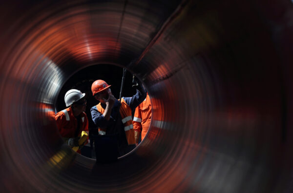 FILE PHOTO: Workers are seen through a pipe at the construction site of the Nord Stream 2 gas pipeline in Russia