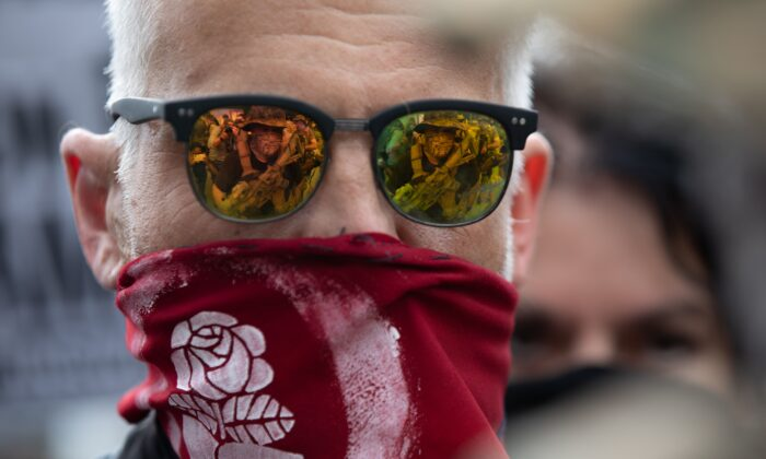 A militia member is seen reflected in the glasses of an Antifa demonstrator during a rally and counter-demonstration in Stone Mountain, Ga., on Aug. 15, 2020. (Logan Cyrus/AFP via Getty Images)