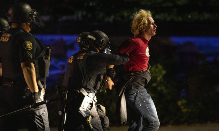 Portland police officers arrest Kristopher Michael Donnelly amid rioting outside a police precinct, in Portland, Ore., Aug. 30, 2020. (Paula Bronstein/AP Photo)
