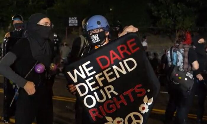 In this still image from video, demonstrators stand near the Penumbra Kelly Building in Portland, Ore., on Sept. 3, 2020. (Roman Balmakov/The Epoch Times)