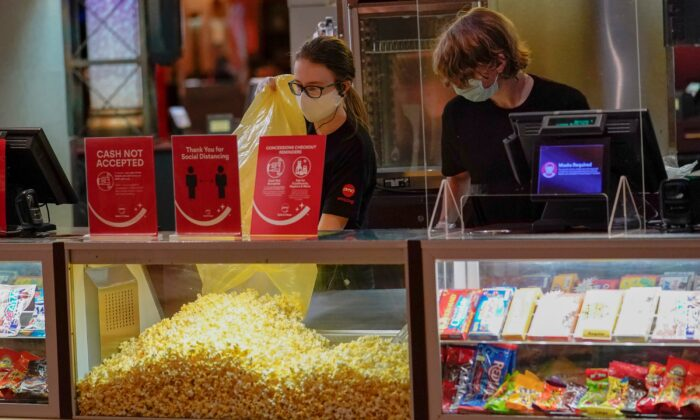 Concessions workers stock the bins with popcorn and other treats as the theatre opens for some of the first showings at the AMC theatre when it re-opened for the first time since shutting down at the start of the COVID-19 pandemic, in West Homestead, Penn., on Aug. 20, 2020. (Keith Srakocic/AP Photo)