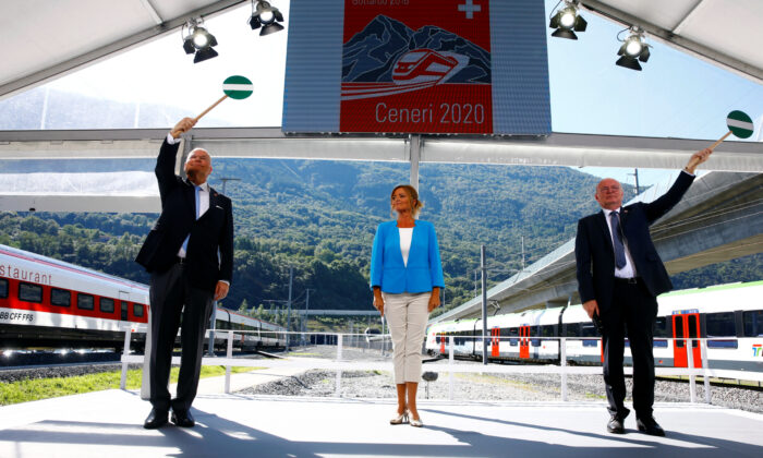 CEO of Swiss Federal Railways (SBB) Vincent Ducrot (R) and CEO AlpTransit Gotthard Dieter Schwank wave signalling discs during the opening ceremony of the newly built Ceneri Base Tunnel, on Sept. 4, 2020. (Arnd Wiegmann/Reuters)