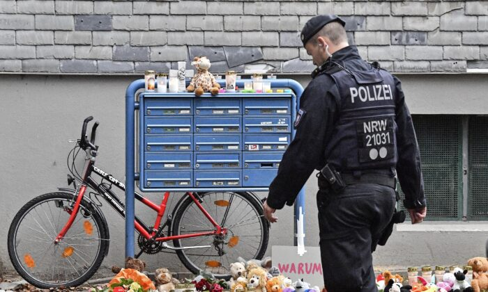 Police passes candles and teddy bears at the entrance of a house where five dead children were found in Solingen, Germany, on Sept. 4, 2020. (Martin Meissner/AP Photo)