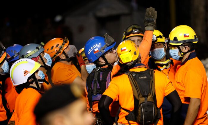The leader of the Chilean rescuers, center, gives his team direction in where to start searching the site of a collapsed building after getting signals there may be a survivor under the rubble, in Beirut, Lebanon, on Sept. 4, 2020. (Hussein Malla/AP Photo)