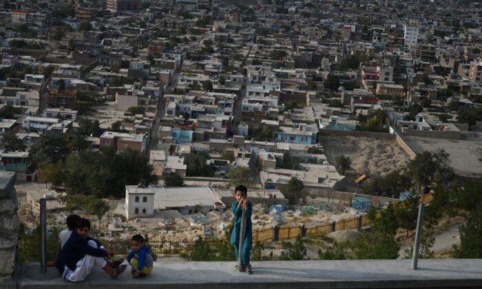 Children react as they sit on a path at Wazir Akbar Khan hilltop overlooking Kabul on Sept. 29, 2019. (Sajjad Hussain/AFP via Getty Images)