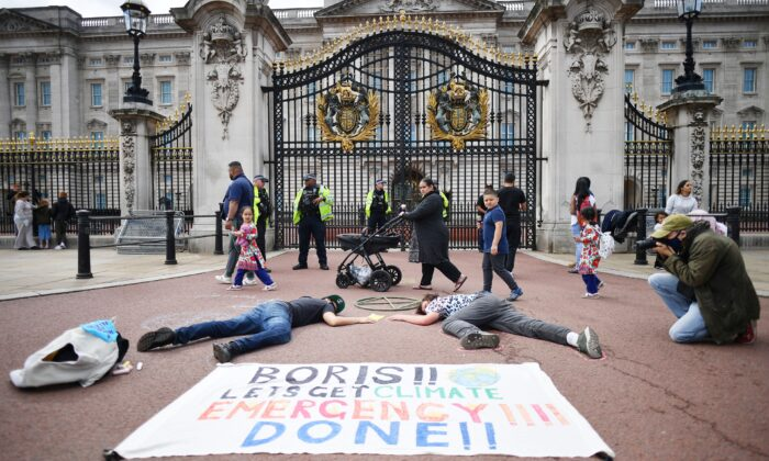 A family walk past as activists take part in a demonstration outside Buckingham Palace, as part of protests by the Extinction Rebellion climate change group on the fifth day of their new series of 'mass rebellions', in central London, on Sept. 5, 2020. (Justin Tallis/AFP via Getty Images)