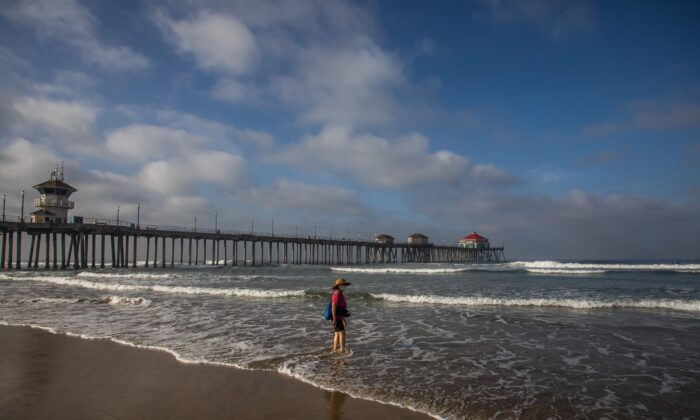 A woman wearing face masks watches the ocean in Huntington Beach, Calif., on May 02, 2020. (Apu GOMES/AFP via Getty Images)