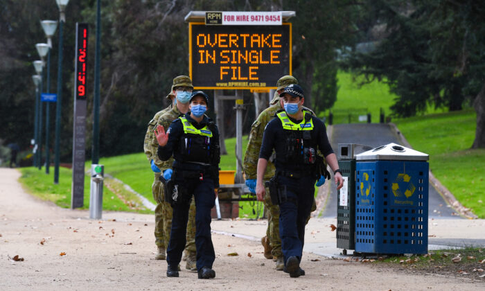 Police officers and soldiers patrol a popular running track in Melbourne, Australia on Aug. 4, 2020. William West / AFP via Getty Images)