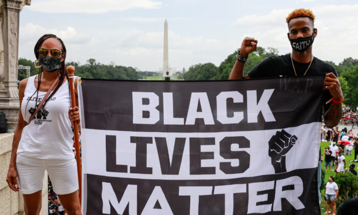 Protesters hold a sign in support of Black Lives Matter during the Commitment March in Washington, D.C. on Aug. 28, 2020.  (Natasha Moustache/Getty Images)