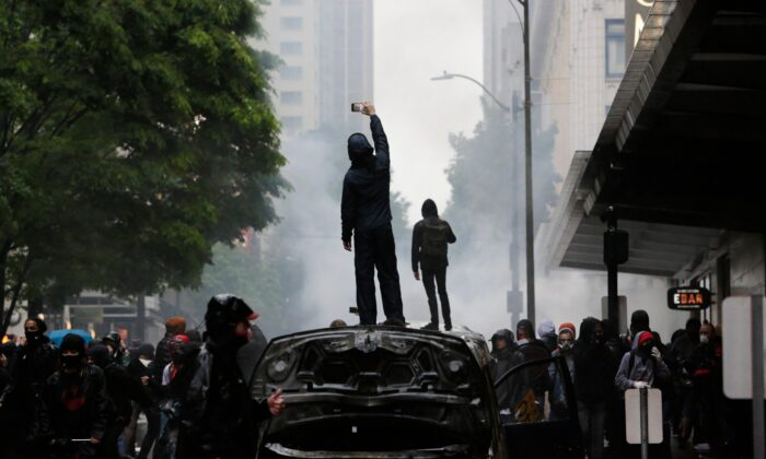 People stand on burned vehicles following demonstrations protesting in Seattle, Wash. on May 30, 2020. (Jason Remond/AFP via Getty Images)