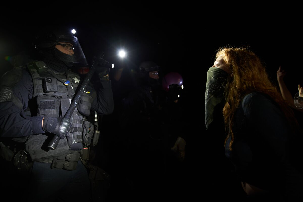 A woman yells at Oregon State Police troopers in Portland, Ore., on Sept. 4, 2020. (Nathan Howard/Getty Images)