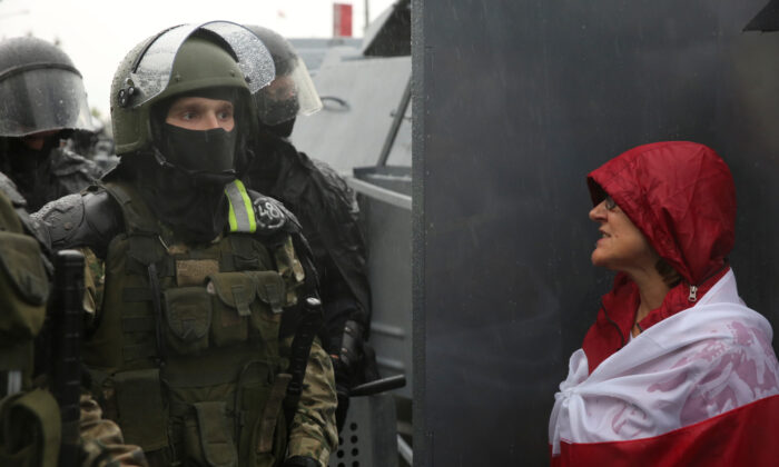 A participant addresses a Belarusian service member during an opposition rally to protest against police brutality and to reject the presidential election in Minsk, on Sept. 6, 2020. (Tut.By via Reuters)