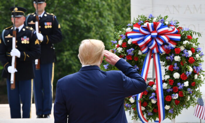 President Donald Trump salutes as he participates in a wreath laying ceremony at the Tomb of the Unknown Soldier at Arlington National Cemetery to commemorate Memorial Day and honor those who have died while serving in the U.S. Armed Forces in Arlington, Virginia on May 25, 2020. (Nicholas Kamm/AFP via Getty Images)