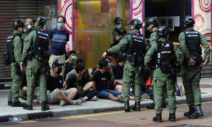People, sitting on the ground, are arrested by police officers at a downtown street in Hong Kong, on Sunday, Sept. 6, 2020. (Vincent Yu/AP Photo)