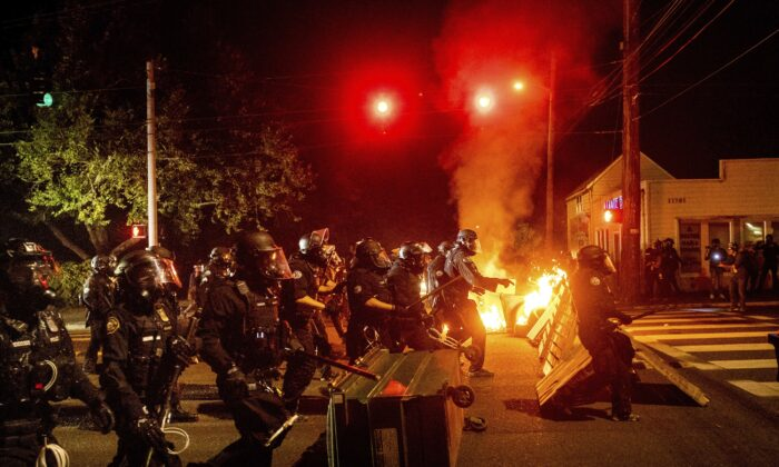 Police officers pass a fire lit by rioters in Portland, Ore. on Sept. 5, 2020. (Noah Berger/AP Photo)