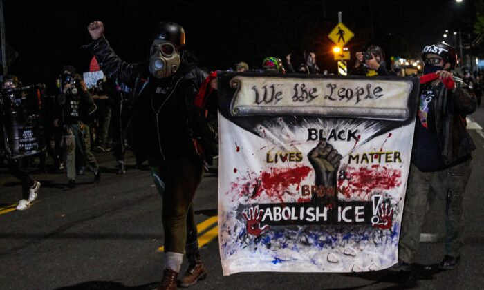 People carry a banner during a march that devolved into a riot in Portland, Ore., late Sept. 5, 2020. (Allison Dinner/AFP via Getty Images)