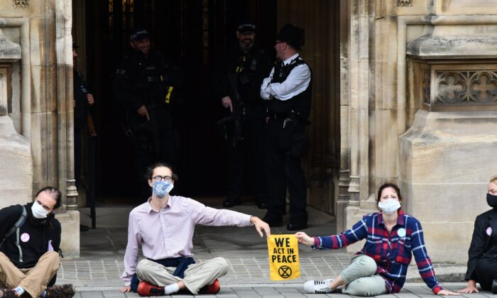 Activists from the climate protest group Extinction Rebellion sit glued to the pavement in front of one of the entrances to the Houses of Parliament in London on Sept. 3, 2020 (Justin Tallis/AFP via Getty Images)