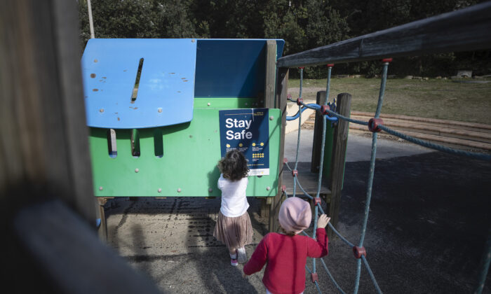 Children look at at COVID-19 related sign at Clovelly playground in Sydney, Australia on May 17, 2020. (Ryan Pierse/Getty Images)
