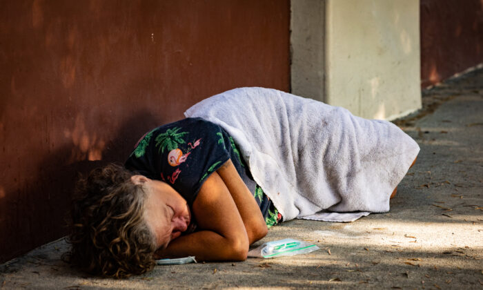 A homeless individual sleeps on the streets of Santa Ana, Calif., on Sept. 4, 2020. (John Fredricks/The Epoch Times)