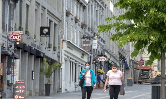 People walk past closed restaurants and bars in Old Montreal on June 4, 2020. (The Canadian Press/Ryan Remiorz)