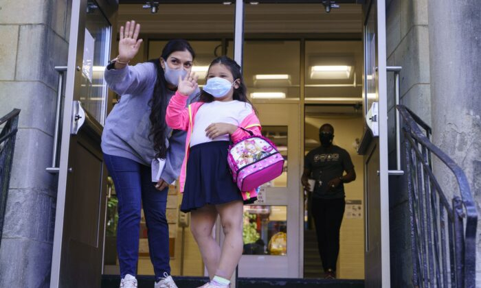 A child waves to her parents at the entrance to Bancroft Elementary School as students go back to school in Montreal on Aug. 31, 2020. (The Canadian Press/Paul Chiasson)