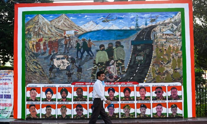 A man walks past a poster depicting portraits of Indian soldiers killed in a hand-to-hand fight with their Chinese counterparts in Ladakh on June 15, in a market area in New Delhi on Aug. 31, 2020.   (Jewel Samad/ AFP via Getty Images)