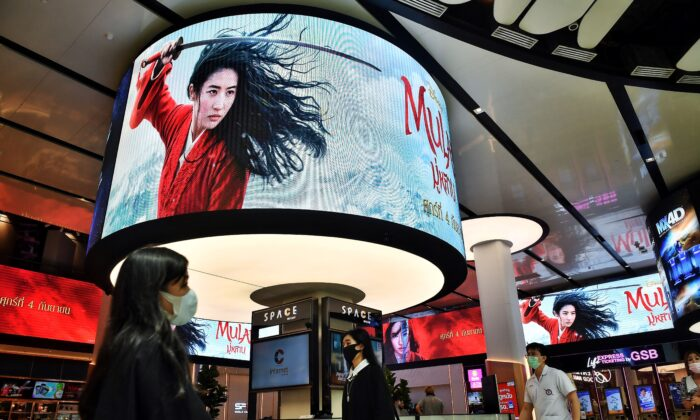 People walk past advertising displays for Disney's Mulan film at a cinema inside a shopping mall in Bangkok on Sept. 8, 2020. (Lillian Suwanrumpha/AFP via Getty Images)