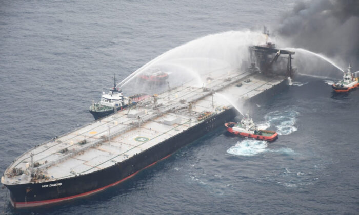 A Sri Lankan Navy boat sprays water on the New Diamond, a very large crude carrier (VLCC) chartered by Indian Oil Corp (IOC), that was carrying the equivalent of about 2 million barrels of oil, after a fire broke out off east coast of Sri Lanka, on Sept. 8, 2020. (Sri Lankan Airforce media/Handout via Reuters)