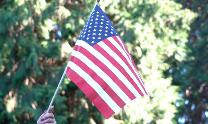 """A person holds up a U.S. flag at a memorial event for Aaron """"Jay"""" Danielson at Esther Short Park in Vancouver, Washington, on Sept. 5, 2020. (The Epoch Times)"""