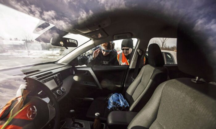 An RCMP officer and a Citizens on Patrol volunteer check a car for valuables to warn the owner about the risk of leaving valuables in a vehicle, in Ardrossan, Alta., on March 6, 2018. (The Canadian Press/Jason Franson)