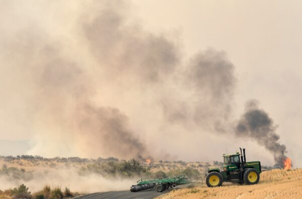 A local man runs a tractor to carve out an impromptu fire line