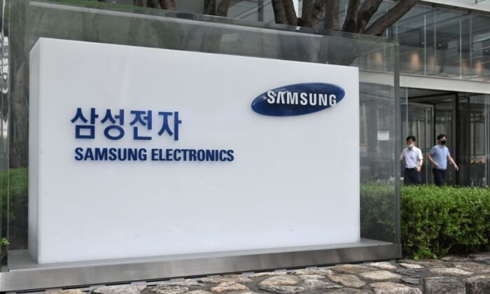 People walk past the logo of Samsung Electronics at the company's Seocho building in Seoul, South Korea, on July 30, 2020. (Jung Yeon-je/AFP via Getty Images)