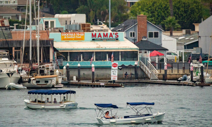 Boats travel in front of Mama's restaurant in Newport Beach, Calif., on Sept. 8, 2020. (John Fredricks/The Epoch Times)