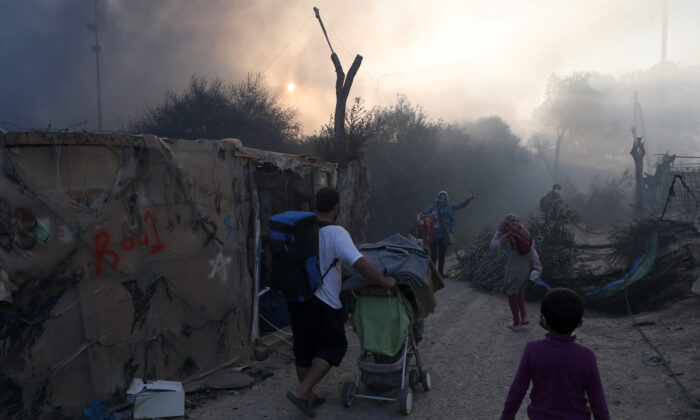 Refugees and migrants carry their belongings as they flee a fire burning at the Moria camp on the island of Lesbos, Greece, on Sept. 9, 2020. (Elias Marcou/Reuters)