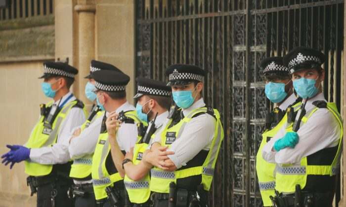 Police officers stand wearing facemasks as a precaution against the transmission of CCP virus, in London, on Sept. 9, 2020. (Isabel Infantes/AFP via Getty Images)