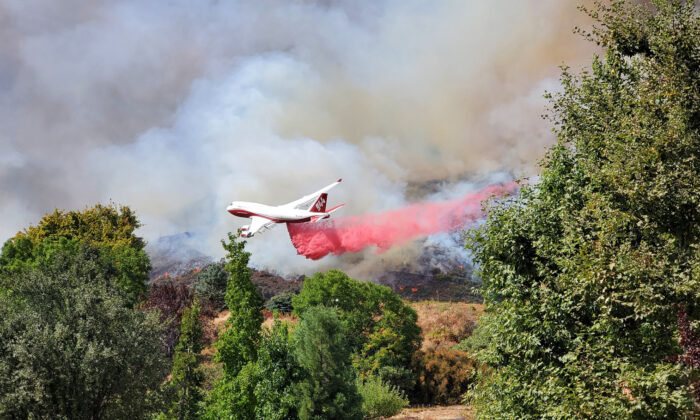 An airplane drops dampening material on a wildfire in San Bernardino County, Calif., on Sept. 5, 2020. (Courtesy of a local photographer on the scene)