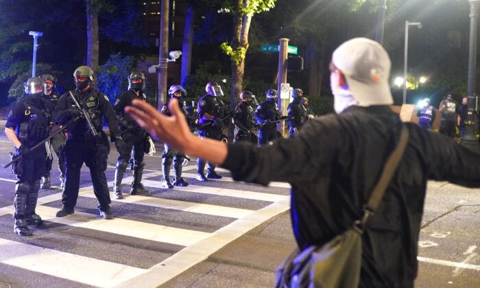 A protester taunts police as they disperse a crowd of about 150 people from around Portland City Hall, in Portland, Ore., on Aug. 25, 2020. Protests and riots have been a nightly occurrence in the city since May. (Nathan Howard/Getty Images)
