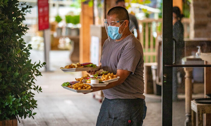A waiter wearing protective face gear balances plates of food on his arms as he carries them to diners at a restaurant in Newport Beach, Calif., on Sept. 9, 2020. (John Fredricks/The Epoch Times)