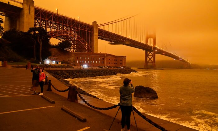 People stop at Fort Point to take morning pictures of the Golden Gate Bridge covered in smoke from wildfires in San Francisco, Calif., on Sept. 9, 2020. (Eric Risberg/AP Photo)