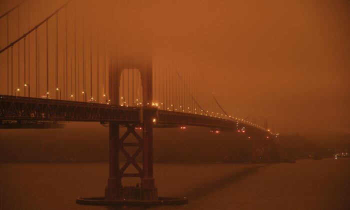 Cars drive along the San Francisco Bay Bridge under an orange smoke filled sky at midday in San Francisco, California on Sept. 9, 2020. (Harold Postic/AFP via Getty Images)