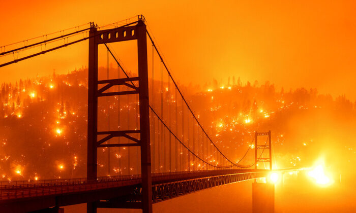 In this image taken with a slow shutter speed, embers light up a hillside behind the Bidwell Bar Bridge as the Bear Fire burns in Oroville, Calif., on Sept. 9, 2020. (AP Photo/Noah Berger)