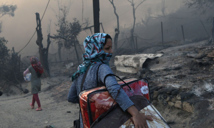 A migrant carries her belongings following a fire at the Moria camp for refugees and migrants on the island of Lesbos, Greece, Sept. 9, 2020. (Elias Marcou/Reuters)