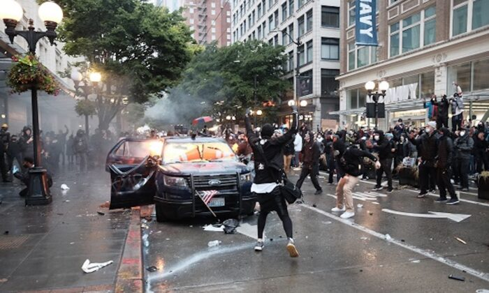 Image shows Kelly Thomas Jackson, 20, throwing a Molotov cocktail at a vehicle during a violent protest in downtown Seattle, Washington, on May 30. (US District Court for the Western District of Washington at Seattle)