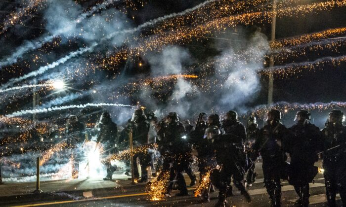Oregon State Troopers and Portland police advance through tear gas while responding to a riot in Portland, Ore., on Sept. 5, 2020. (Nathan Howard/Getty Images)