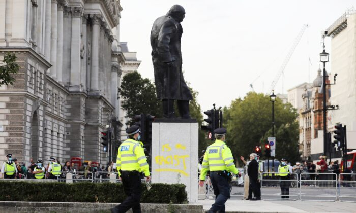 Police officers walk by the defaced statue of Winston Churchill, in London, on Sept. 10, 2020. (Simon Dawson/Reuters)