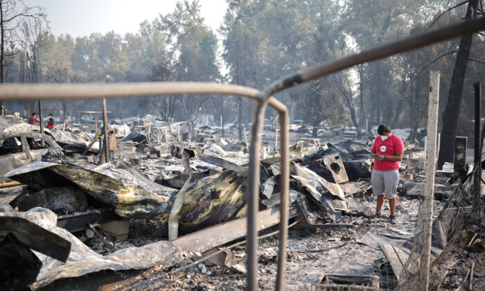 A man inspect a neighborhood after wildfires destroyed an area of Phoenix, Ore., on Sept. 10, 2020. (Carlos Barria/Reuters)